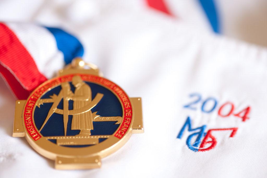 Médaille Meilleur Ouvrier de France Pâtissier-confiseur sur veste de cuisine au col tricolor