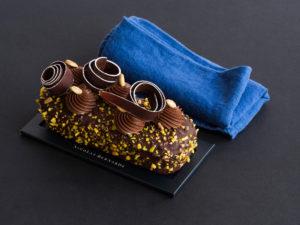 Cakissime chocolat et pistache enrobé de chocolat sur un fond noir