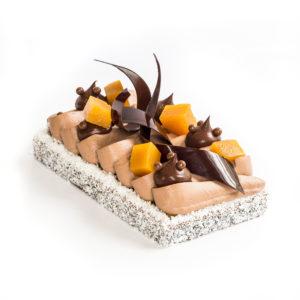 Entremets mangue, fruits de la passion et chocolat, entouré de copeaux de noix de coco