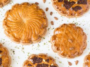 Collection de galettes des rois aux amandes ou au chocolat-pistache, vues de haut sur un fond blanc