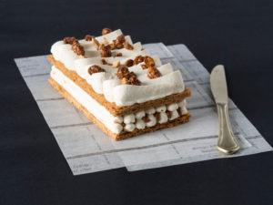 Millefeuille vanille cacahuete sur fond noir, un couteau est posé à côté