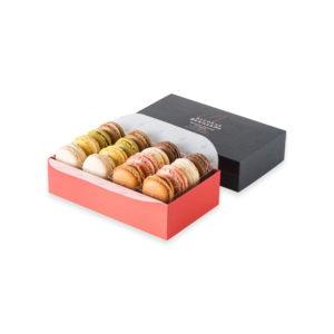 Assortiment de 16 macarons, dans une boite rectangulaire rouge en carton et son couvercle noir