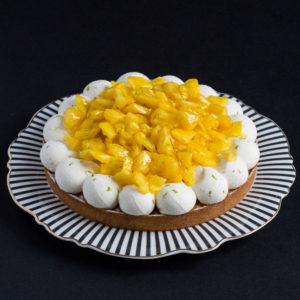 Tarte Bahia, ananas passion sur une assiette rayée, devant un fond noir