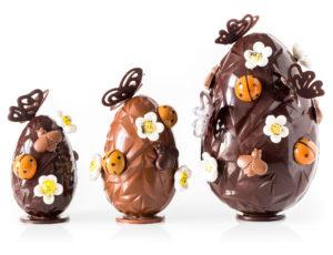 Trois œufs en chocolat côté à côté, sur un fond blanc. Chacun est décoré de fleurs et de papillons en chocolat