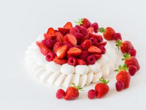 Pavlova et gâteaux sur commande, entouré de fruits rouges
