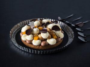 Tarte profiterole chocolat passion sur un fond noir