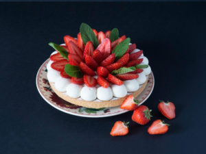 Sur un fond noir, un Sablé breton surmonté d'une ribambelle de fraises fraiches entouré de crème vanille, posé sur une assiette décorée devant laquelle sont posées des morceaux de fraises fraiches