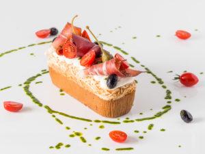 Cakissime Rimini, cake salé surmonté de cheese cream, tomates confites, olives et jambon Serrano, entouré d'un décor de pesto et de tomates cerises
