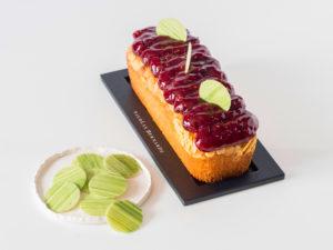 Cake amande et framboise, devant un panier de framboises bien rouges