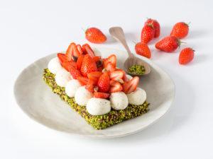 Papa pistache : entremets fraise pistache de la fête des pères 2021, gâteau dans une assiette blanche, entourée de fraises garrigue ttes fraiches