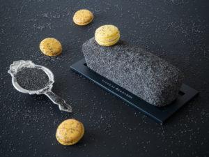 Sur fond noir, un cake au citron entièremen recouvert de pavot, surmonté d'un macaron au citron. à côté une passoire ancienne remplie de graines de pavot