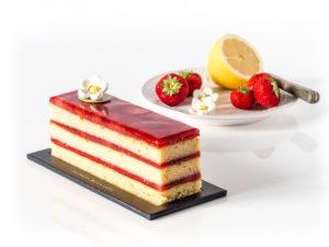 cake fraise citron à étages devant une assiette blanche rem^plie de citron et de fraises fraiches, sur un fond blanc
